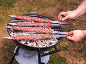 A chef putting red meat shish kebab onto a charcoal barbecue — Foto Stock