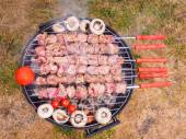 Shish kebab prepared over a black round shaped charcoal barbecue — Stock Photo