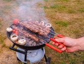 Closeup of a chef turning skewers of meat on hot barbecue — Stock fotografie