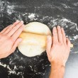 Person handling a dough with a rolling pin floured black table — Stock Photo #57108385
