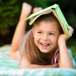 Little girl is hiding under book outdoors — Stock Photo #52109953