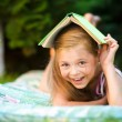 Little girl is hiding under book outdoors — Stock Photo #52156899