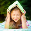 Little girl is hiding under book outdoors — Stock Photo #52246385