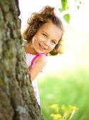 Schattig klein meisje is spelen verstoppertje en zoeken — Stockfoto