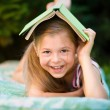 Little girl is hiding under book outdoors — Stock Photo #52285765