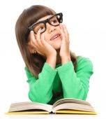 Young girl is daydreaming while reading book — Stock Photo