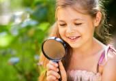 молодая девушка смотрит на цветок через лупу — Стоковое фото
