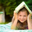 Little girl is hiding under book outdoors — Stock Photo #52806833