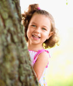 Cute little girl is playing hide and seek — Stock Photo
