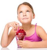 Happy little girl is eating raspberries — Stock Photo
