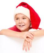 Little girl in santa hat is holding blank board — Stock Photo