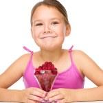 Happy little girl is eating raspberries — Stock Photo #56292517