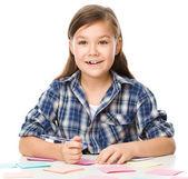 Девочка пишет на цветных этикетках, используя ручку — Стоковое фото