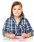 Girl is writing on color stickers using pen — Foto de Stock