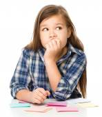Girl is writing on color stickers using pen — Stockfoto