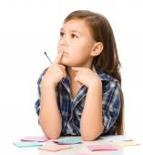 Girl is writing on color stickers using pen — Stok fotoğraf