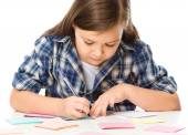 Girl is writing on color stickers using pen — Photo