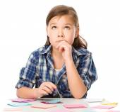 Girl is writing on color stickers using pen — Stock Photo