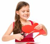 Portrait of a little girl cutting out red heart — Stock Photo