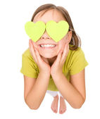 Little girl is holding hearts over her eyes — Stock Photo