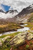 Vista a neve sobre as montanhas do cáucaso, através de fluxo de águas claras perto — Fotografia Stock