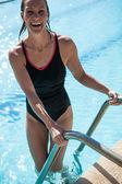привлекательный счастливый пловец женского пола на лестнице в бассейне края — Стоковое фото