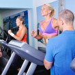Two women in gym exercising with personal fitness trainer — Stock Photo #57076765