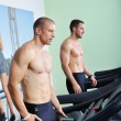 Two handsome men in gym running on the ergometer — Stock Photo #57076895