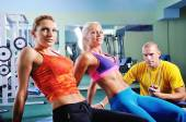 Woman in gym exercising with personal fitness trainer — 图库照片