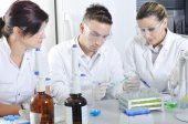 Attractive young PhD students scientists observing in the labora — Stock Photo
