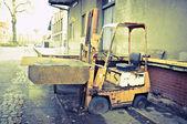 Vintage old broken forklift standing on flat tires — Stock Photo