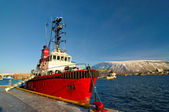 Norwegian fishing boat parked in a harbor in Tromso, city in northern Norway. City landscape with mountain and Arctic Cathedral in background — ストック写真