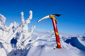 Red ice pickaxe in a fresh white snow in the mountains — Stock Photo