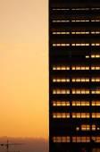 Deconstruction of old office building. Sunset light in background going through skeleton of  broken windows. — Stock Photo