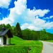Very small chapel next to the country road leading to a forest in Bavaria, Germany. Under a blue sky and white clouds. — Stock Photo #78063300