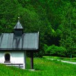 Very small chapel next to the country road leading to a forest in Bavaria, Germany. Under a blue sky and white clouds. — Stock Photo #78063320
