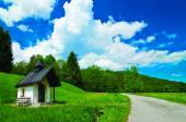 Very small chapel next to the country road leading to a forest in Bavaria, Germany. Under a blue sky and white clouds. — Stock Photo