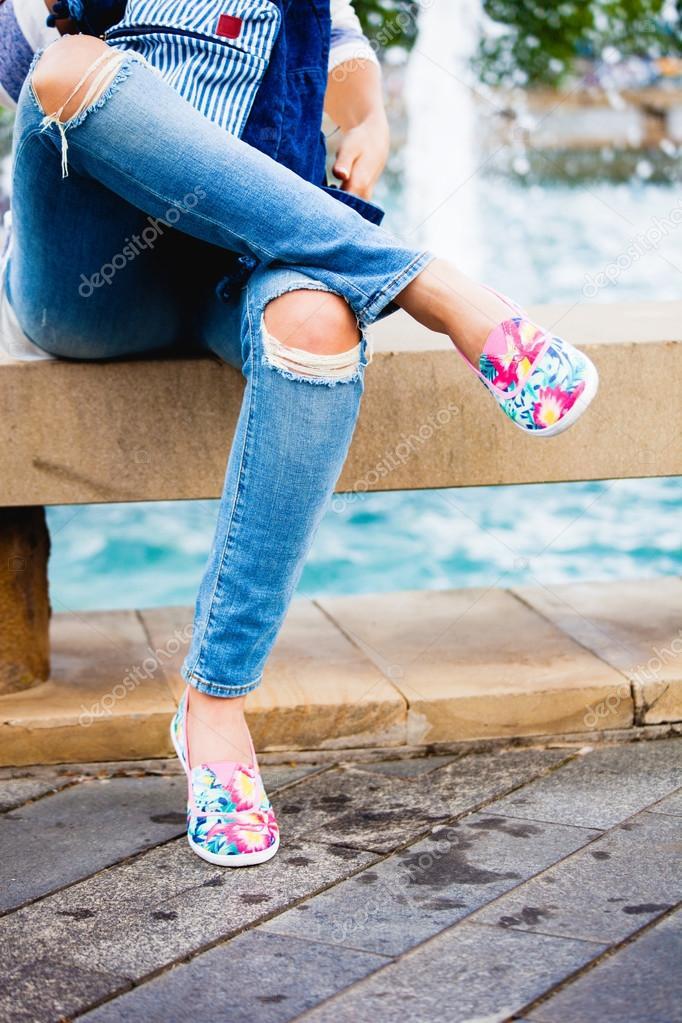 Chica en jeans azul y alpargatas sentado junto a fuente de la ciudad día de verano\u2014 Foto de cokacoka