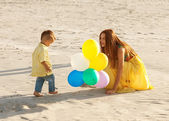 Happy mother and son on the beach sunset — Stock Photo