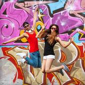 Fashion couple in sunglasses standing near a graffiti wall — Stock Photo