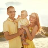Hermosa familia feliz en el sunset beach — Foto de Stock