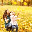 Mother and daughter having fun in the autumn park among the fall — Stock Photo #54337943