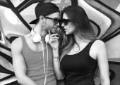 пара моды с солнцезащитные очки возле стены граффити — Стоковое фото
