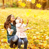 Mother and daughter having fun in the autumn park among the fall — Stock Photo