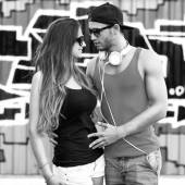 Fashion couple with sunglasses near the wall graffiti — Stock Photo