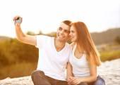 Loving couple taking selfie in the park — Stock Photo