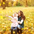 Mother and daughter having fun in the autumn park among the fall — Stock Photo #57554499
