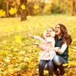 Mother and daughter having fun in the autumn park — Stock Photo #57555283