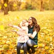 Mother and daughter having fun in the autumn park among the fall — Stock Photo #57555343