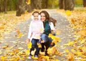 Mother and daughter having fun in the autumn park — Stock Photo